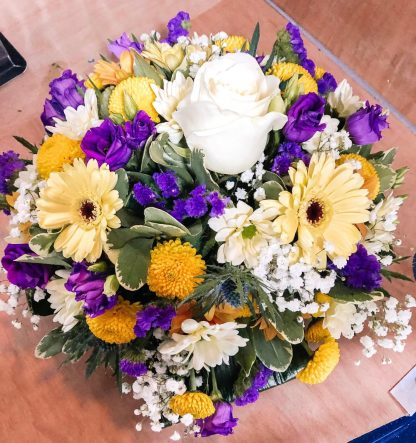 Round posy showing flowers in a mix of yellow, whites & purples. WIth a beautiful centre rose in white.