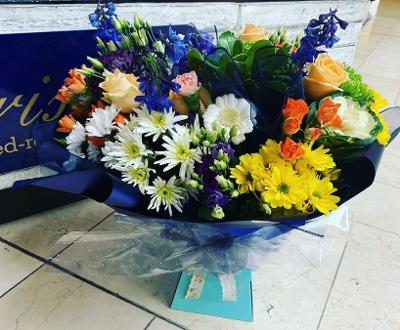 Aqua Bouquet with a mix of seasonal flowers in blue, purple. yellow, cream & oranges.
