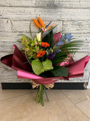 A handtied bouquet showing a mix of exotic flower presented in a luxury wrap with bow