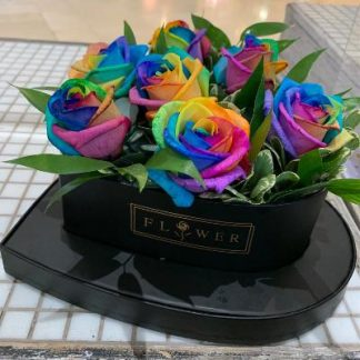 Side view of rainbow roses in a black heart shaped rose box.