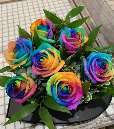 7 Rainbow Roses in the shape of a heart on a black heart shaped base.