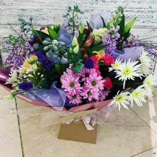 Aqua Bouquet with a mix of seasonal bright flowers in pink, creams, purple. oranges & yellows.