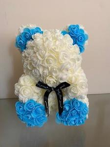 Cream bear with blue paws & ears. complete with a black bow.