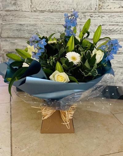 Large aqua bouquet showing an elegant mix of cream roses, white lilies & Delphiniums.