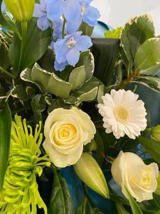 Close up view of cream roses, lilies & Delphinium
