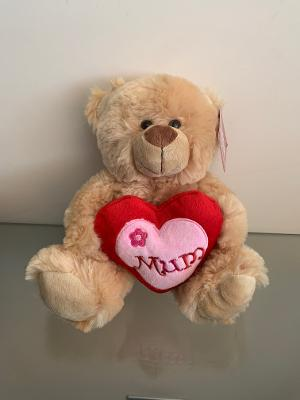Soft brown teddy bear, holding a red heart which says mum on.