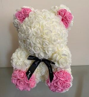 Cream rose bear with pink paws & ears. Finished with a black bow around neck.