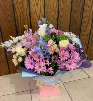 Pretty mix of pastel colour seasonal blooms in a baby pink aqua box with soft blue wrap.