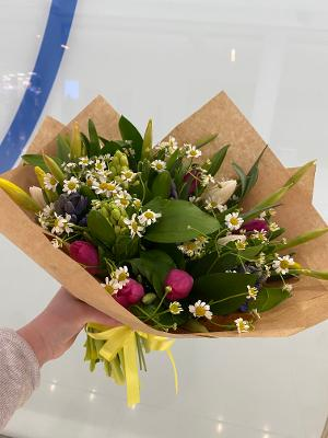 A stunning array of seasonal spring flowers. Presented in a rustic brown wrap with yellow bow.