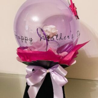 A single white artificial rose presented within a lilac bubble balloon. Presented in a gift box with pink wraps & finished with a decorative butterfly.
