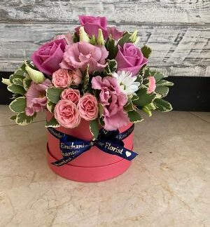 Pink roses presented in a pink hat box with mixed foliage's. Finished with a blue satin bow.