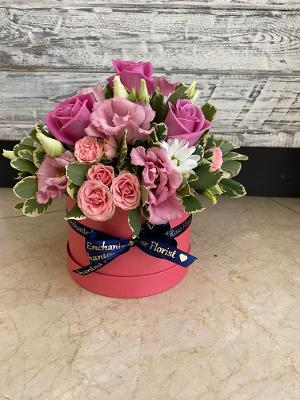 Pink roses in a pink hat box with blue ribbon