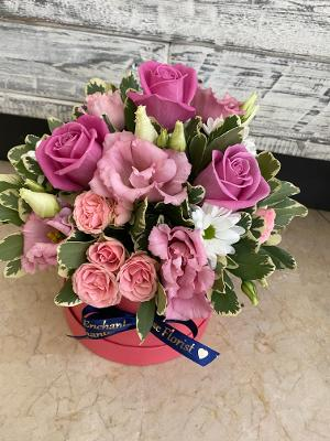 close view of pink roses presented in a pink hat box.